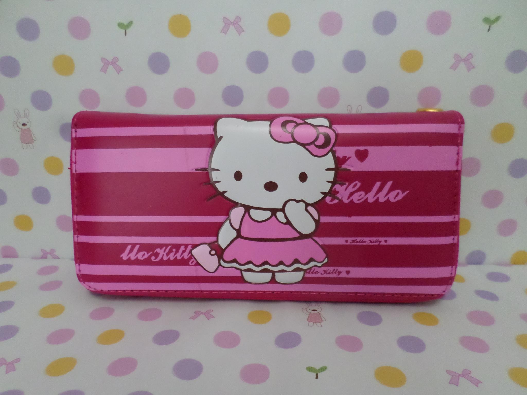 กระเป๋าสตางศ์ทรงยาว ฮัลโหลคิตตี้ Hello Kitty ขนาดยาว 7.5 นิ้ว x สูง 4 นิ้ว ลายคิตตี้ยืนโบว์ชมพู ซิปรอบพร้อมสายคล้องข้อมือ
